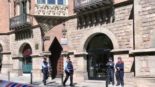 Los Mossos vigilan el exterior del Diplocat mientras era registrado por la Guardia Civil.