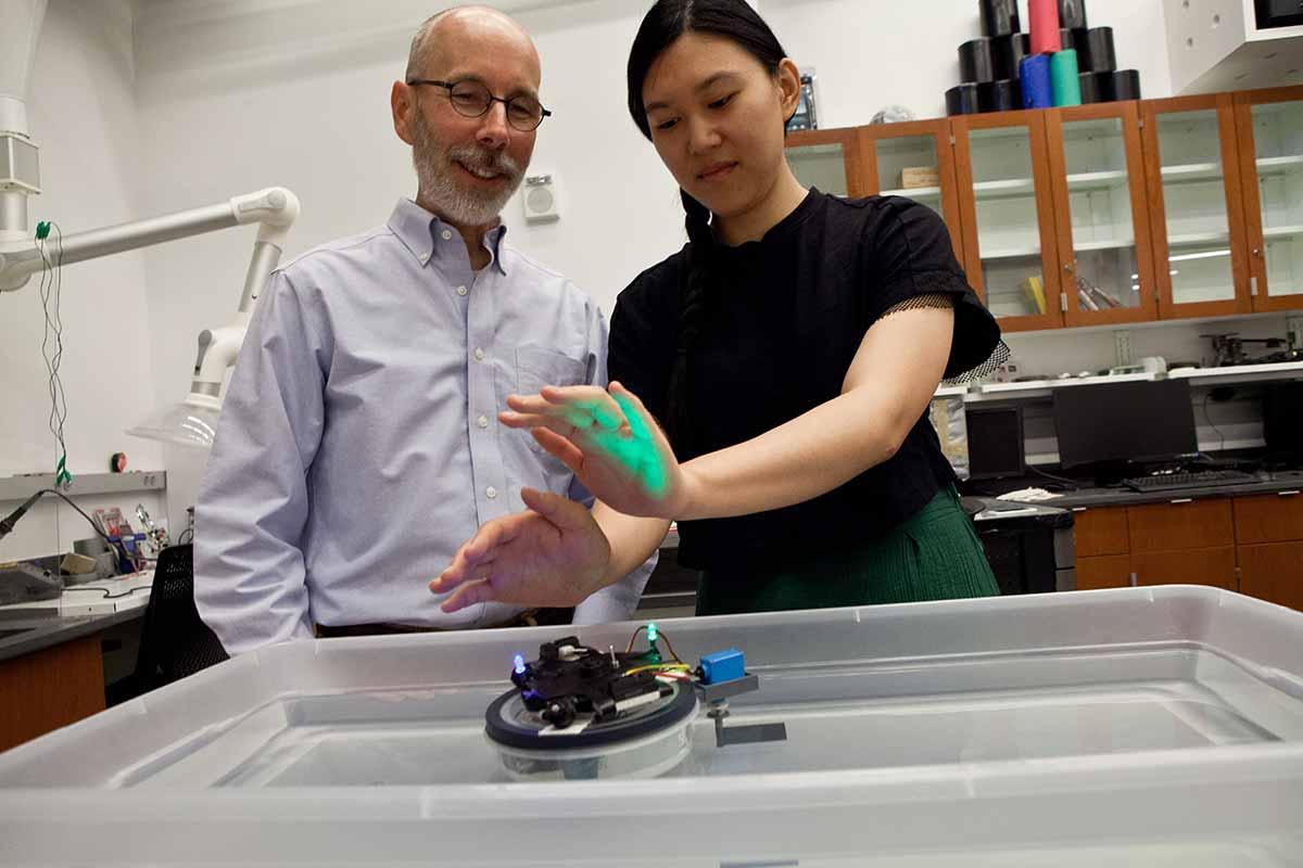 John Long trabajando con uno de sus robots