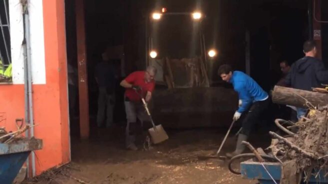Rafael Nadal (de azul), achica agua y lodo de un taller en Sant Llorenç (Mallorca).
