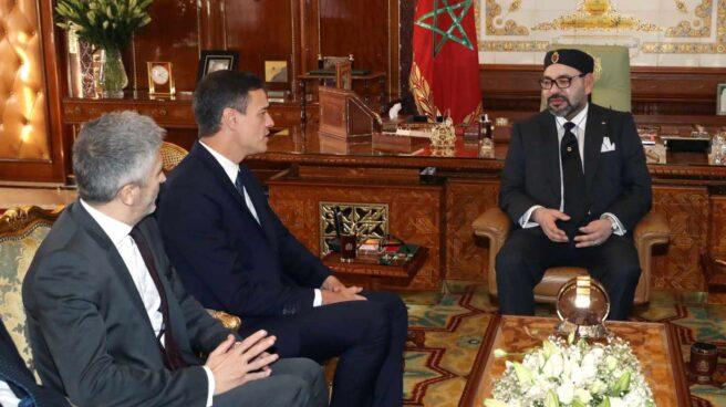 El presidente del Gobierno español, Pedro Sánchez (2i), junto al ministro del Interior, Fernando Grande-Marlaska (i), durante la reunión que ha mantenido hoy con el rey Mohamed VI (c) de Marruecos.