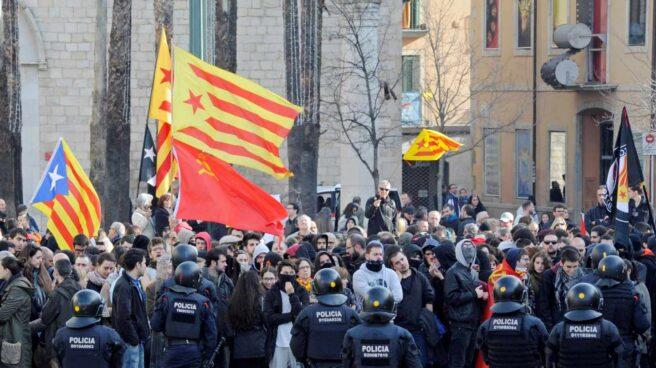 Mossos d'esquadra frente a las numerosas personas, muchas de ellas encapuchadas, que trataban de boicotear los actos conmemorativos de la Constitución en Girona.