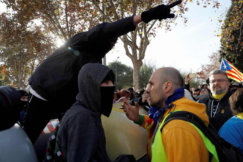 Un manifestante independentista trata de impedir que un grupo de encapuchados vuelquen contenedores