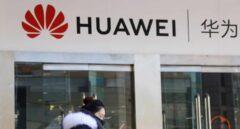 Una china pasa junto a una tienda de móviles Huawei en Pekín.