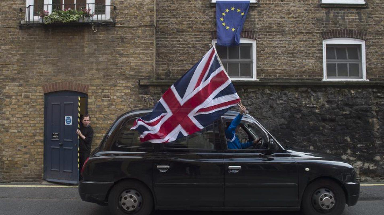 Un taxi con una bandera del Reino Unido pasa delante de una ventana con una bandera de la UE.