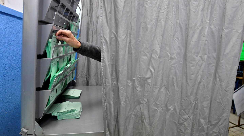 Un votante escoge su papeleta durante la jornada electoral.