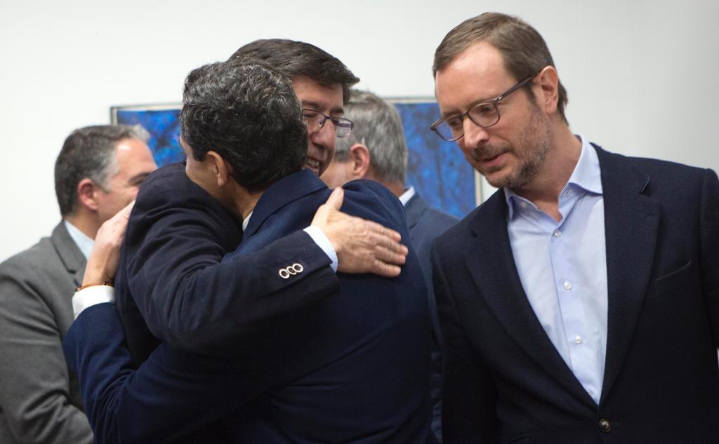 Juan Marín y Juanma Moreno se abrazan ante Javier Maroto en el parlamento andaluz.