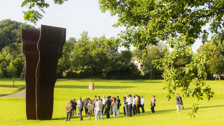 Grupo visitando Chillida Leku bajo la sombra de Buscando la luz I (acero corten, 1997).