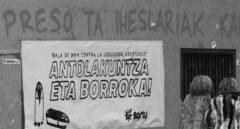 """Dos mujeres pasan frente a una pancarta con el lema """"Bala de 9mm contra la izquierda abertzale""""."""