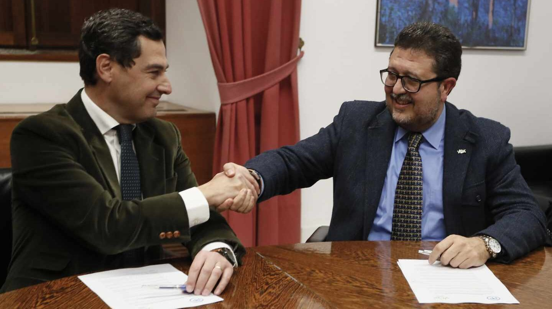 Juan Manuel Moreno estrecha la mano con el líder andaluz de Vox, Francisco Serrano.