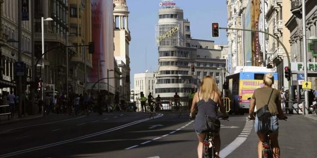 Dos personas circulan en bicicleta por la Gran Vía de Madrid