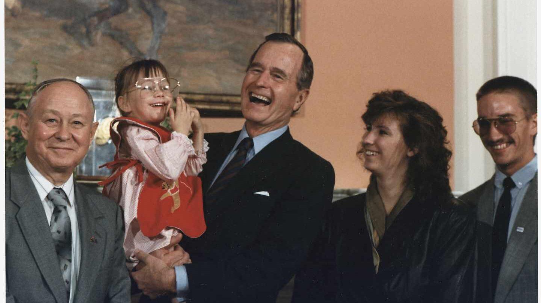 El ex presidente de Estados Unidos, George H.W. Bush sostiene en brazos a Jessica McClute, la niña rescatada de un pozo tras 58 horas atrapada