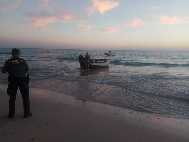 Un agente de la Guardia Civil frente a una patera en el Estrecho.