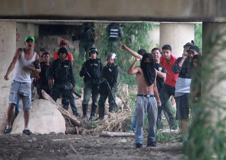 Vista de seguidores del gobierno del presidente de Venezuela, Nicolás Maduro, y miembros de la Policía venezolana durante los enfrentamientos con los manifestantes opositores, en el lado venezolano del Puente Internacional Simón Bolívar, este sábado.
