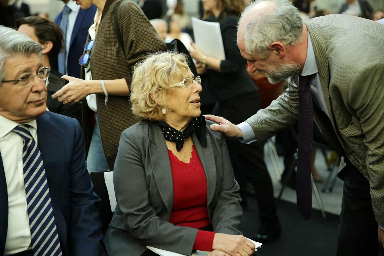 Luis Cueto saluda a Manuela Carmena en presencia de Enrique Cerezo.