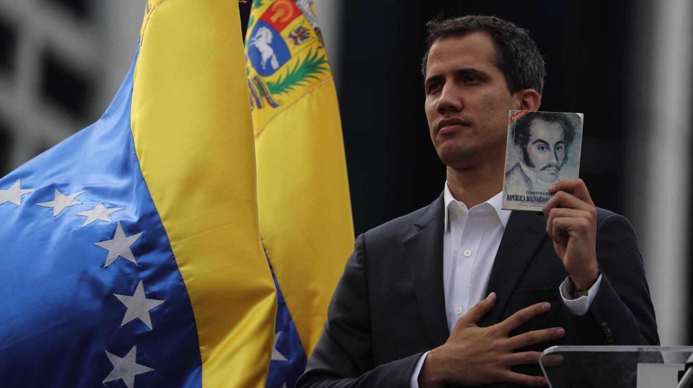 El presidente encargado de Venezuela, Juan Guaidó, muestra un retrato de Simón Bolívar.