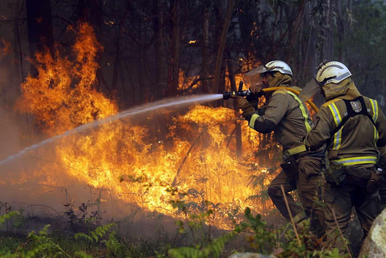 Los bomberos apagan uno de los numerosos focos del incendio en la localidad coruñesa de Rianxo