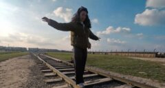Una turista del campo de concentración de Auschwitz haciendo equilibrio sobre las vías férreas