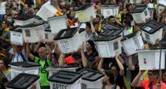 Votantes del 1-O con las urnas.