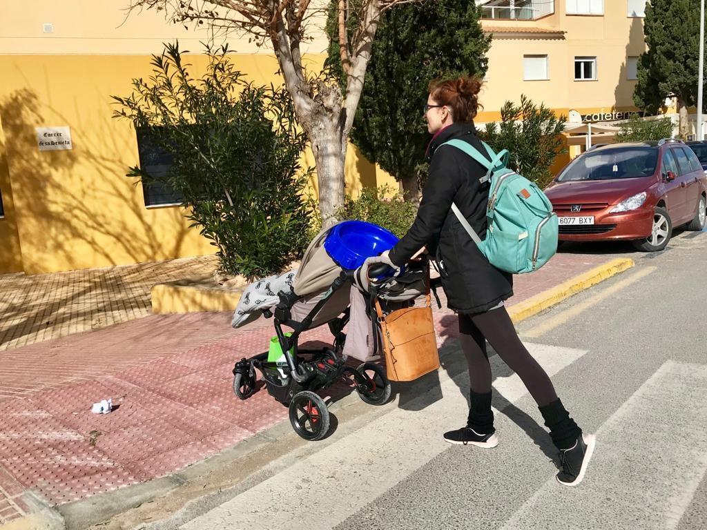 Una mujer cruza un paso de peatones con un carrito de bebé.