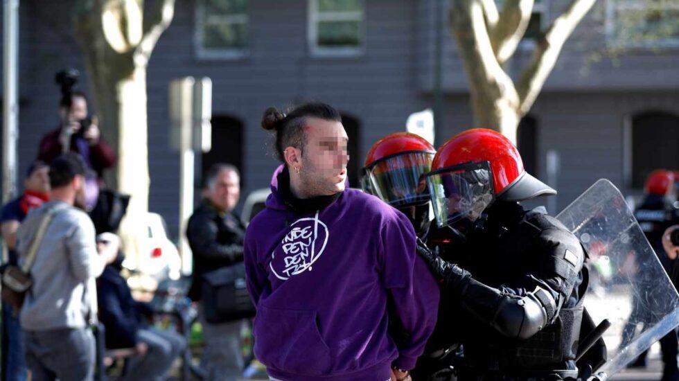 Un joven es detenido por agentes de la Ertzaintza durante la concentración que un centenar de personas han llevado a cabo ante el Palacio Euskalduna de Bilbao, donde esta tarde participa el líder de Vox, Santiago Abascal en un acto electoral.