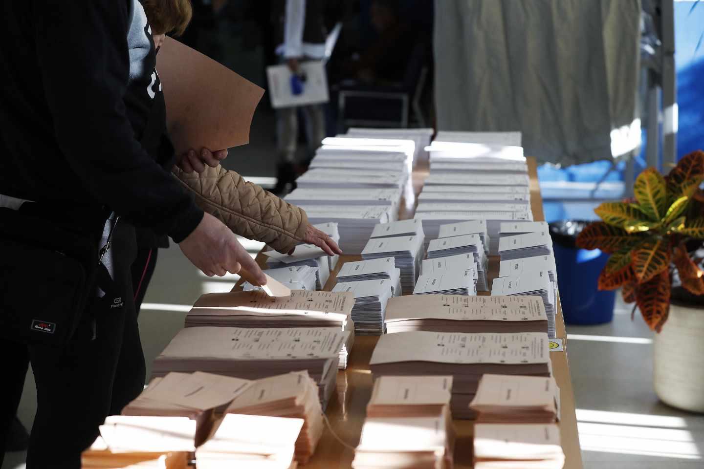 Los colegios electorales han abierto sus puertas a las 09:00 horas para recoger el voto de los casi 36,9 millones de electores que decidirán este domingo en los comicios generales el reparto de los 350 escaños del Congreso de los Diputados y los 208 del Senado durante la próxima legislatura.Tras la constitución de las mesas a las ocho de la mañana con la comprobación de que estaban los miembros necesarios y la lectura de los manuales, a las nueve de la mañana los electores han comenzado a acudir a las urnas, en una jornada que estará marcada por el sol y con temperaturas, en general, al alza en casi todo el país. En la foto, dos personas eligen sus papeletas en electoral en el colegio Pinar del Rey.