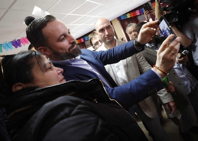 El presidente de VOX y candidato a la presidencia del Gobierno, Santiago Abascal,se hace una foto con una simpatizante tras depositar su voto en el Colegio Público Pinar del Rey,
