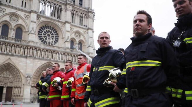 Un grupo de bomberos esperan la llegada del ministro del Interior ante Notre-Dame.