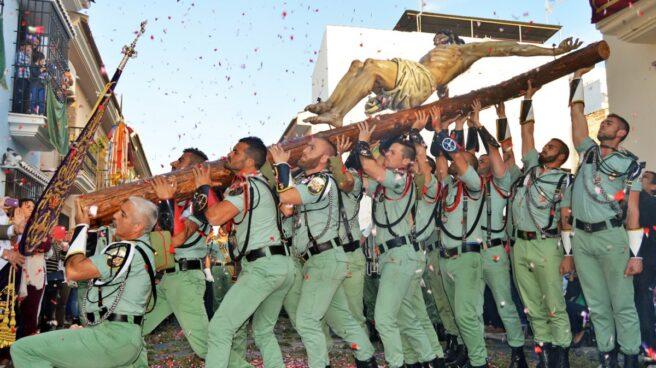 Un grupo de legionarios levanta al Cristo de Mena en Málaga.