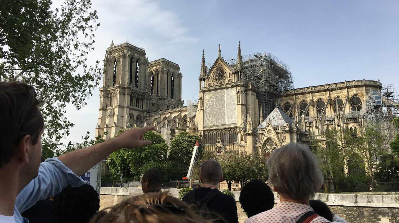 Los turistas se agolpan en el exterior de Notre-Dame para ver el efecto del incendio.
