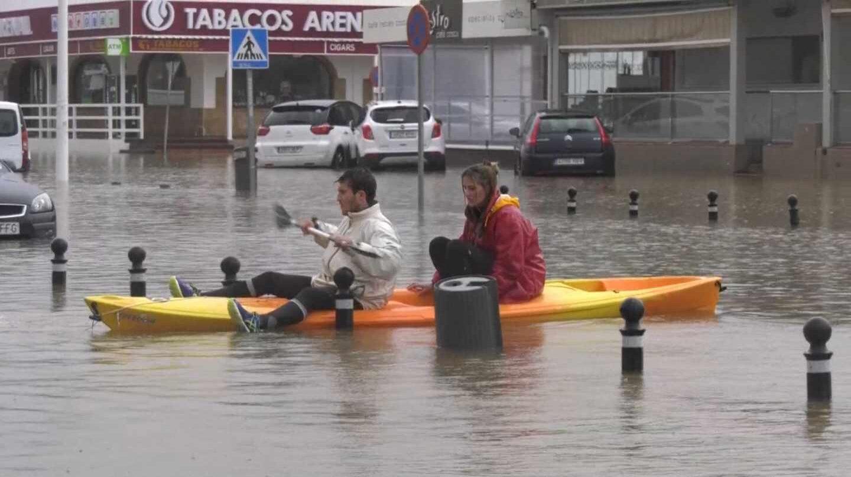 Dos personas navegan en canoa por las calles de Jávea