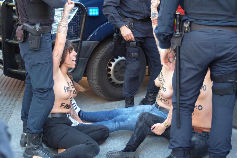 Las activistas de Femen gritan ante los agentes de la Policía.