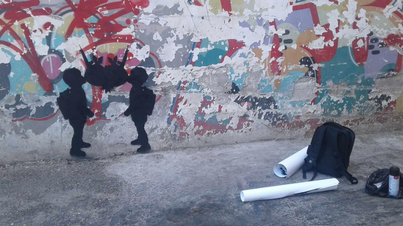 """Dos niños, que representan cada uno de ellos a las partes del conflicto palestino-israelí, se besan simbolizando el amor, la violencia política o, """"simplemente"""", la indiferencia. Dos pompas de chicle, unas granadas y dos armas conforman el corazón que surge de este beso."""