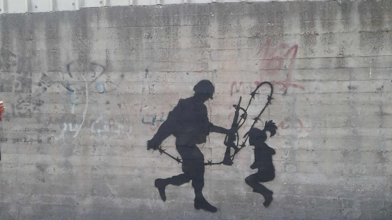Un joven soldado israelí que no quiere servir en el Ejército sostiene la cuerda de espino ante una niña. El grafitero representa la decisión del soldado israelí de herir o no a la pequeña.