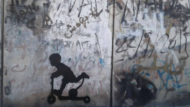 """A través de este niño montado en un patinete y con un grillete con bola enganchado a su tobillo, Cake $ representa """"la ocupación y lucha diaria"""" con la que lidian los palestinos."""