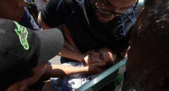 Manifestantes trasladan a una mujer herida de bala en Caracas, Venezuela.