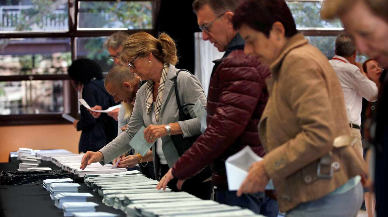 Varios ciudadanos escogen sus papeletas electorales en el Centre Cívic La Sedeta de Barcelona.