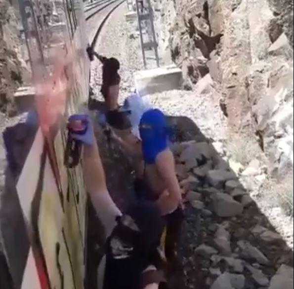 Los grafiteros pintando el tren a la altura de Galapagar, en Madrid.