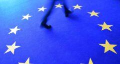 Un hombre pasa por un alfombra con las estrellas de la bandera de la UE.