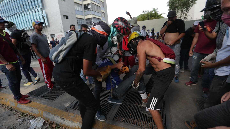 Manifestantes de la oposición ayudan a un herido en las marchas en Caracas.