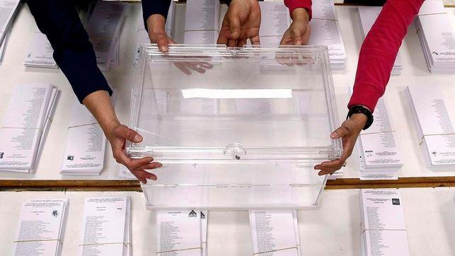 Una urna junto a papeletas en una jornada de elecciones.