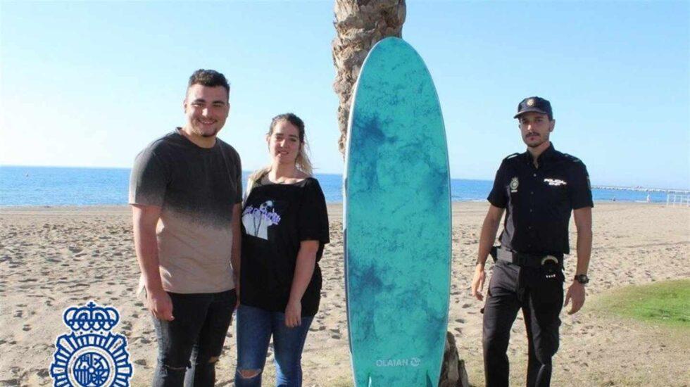 Agente con la tabla de surf y junto a los bañistas.