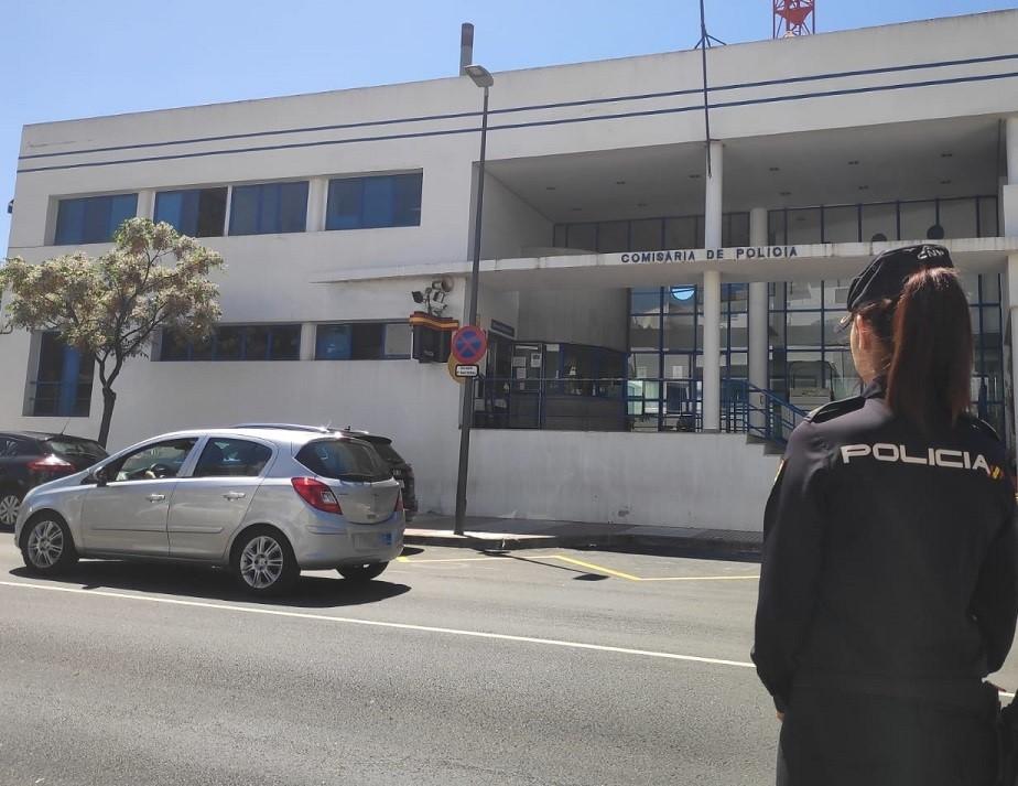 Agente frente a una comisaría de Policía.