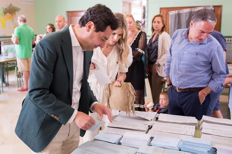 Juan Manuel Moreno busca la papeleta para votar este domingo en el colegio Sagrado Corazón de Málaga.