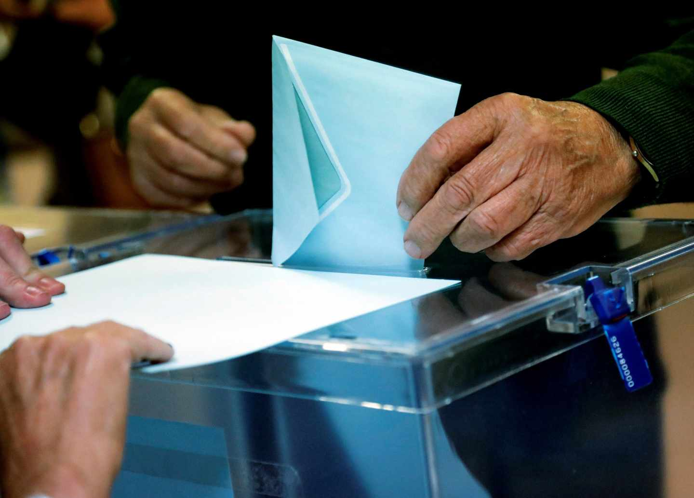 Un ciudadano deposita su voto ante la urna en Madrid.