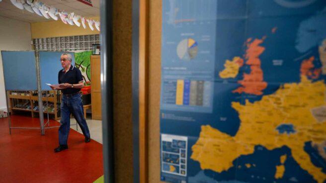 Un votante se dirige a las urnas en un colegio donde se muestra un mapa de Europa.