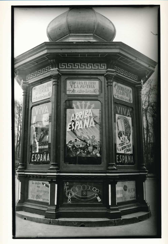 Quiosco de «Gene» (Generosa Ferrera) con carteles de propaganda franquista, en la plaza de la Escandalera. Oviedo, 1937. Florentino López, «Floro». Museo del Pueblo de Asturias FF045868.