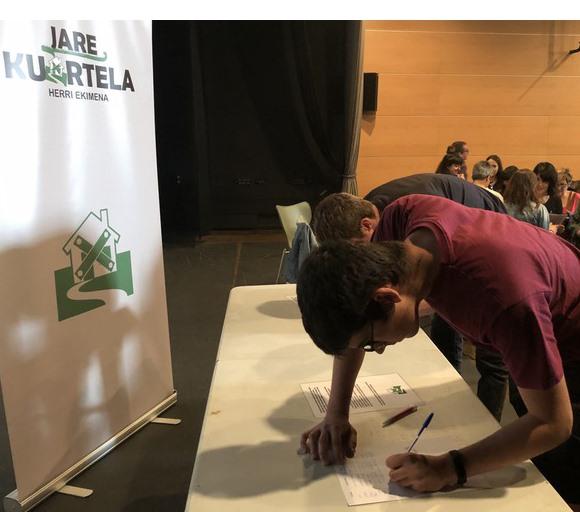 Un joven firma en una de las mesas instaladas por 'Jare Kuartela'.