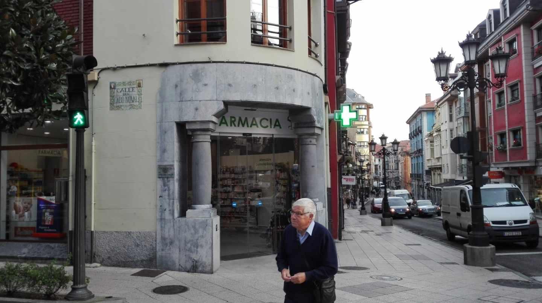 Un pensionista cruza frente a una Farmacia.