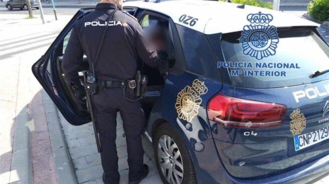 Un agente de la Policía Nacional introduce a un detenido en el vehículo policial