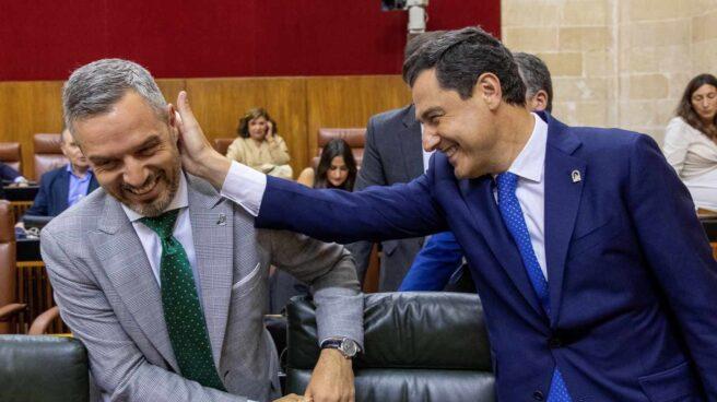 Juanma Moreno bromea con el consejero de Hacienda de la Junta de Andalucía al inicio del pleno.